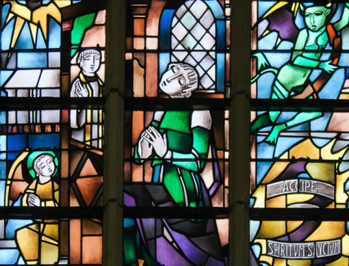Stained glass image of penitent on a Catholic church in Belgium.