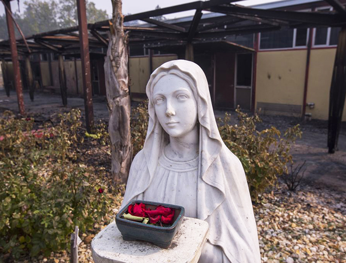 A statue of Our Lady is seen among fire-damaged buildings at Cardinal Newman High School on Oct. 10 in Santa Rosa, California. In one of the worst wildfires in state history, at least 1,500 homes have burned and 11 people have died as more than 14 wildfires continue to spread in eight Northern California counties.