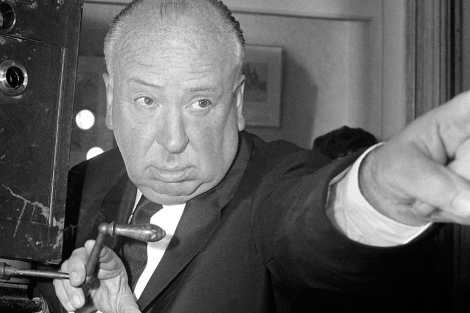 British film director Alfred Hitchcock stands next to an old cinematograph (film camera) at the Cinémathèque Française in Paris, France, on May 28, 1960.
