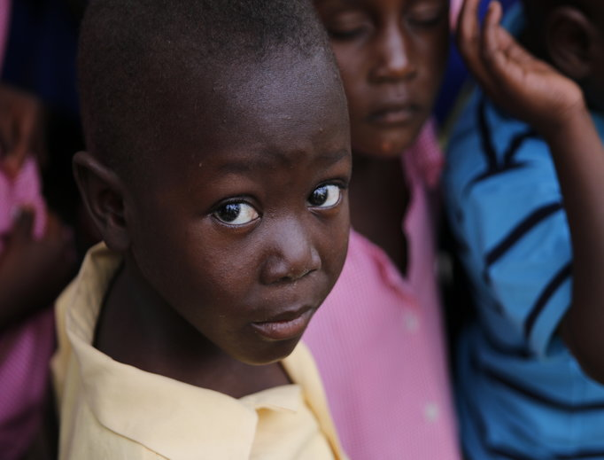 Above and below, Haitian children. Also below, the exterior facade of St. Anne Church in Camp-Perrin, Haiti; Cross Catholic Outreach President James Cavnar hands a 'box of joy' to a child and mother at a school in Camp-Perrin; and first-grade children at Pwoje Espwa's main school open their 'box of joy' presents made possible by Cross Catholic Outreach.
