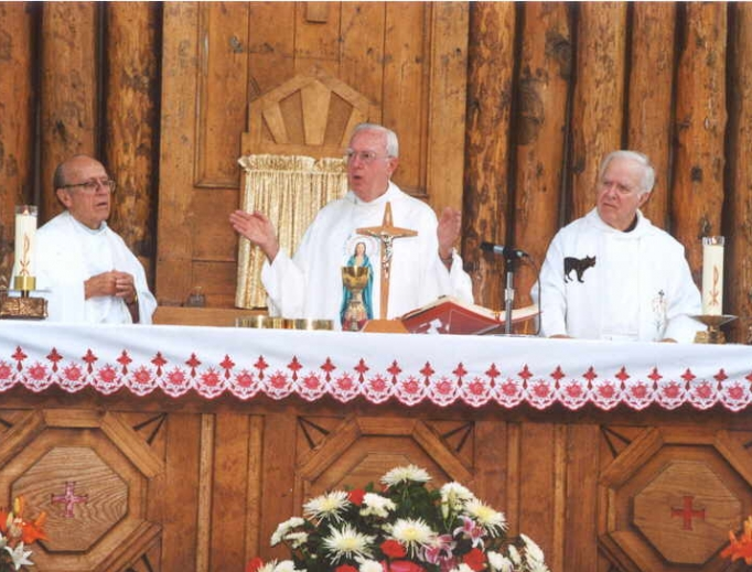 Above, Msgr. Paul A. Lenz concelebrating the Blessed Kateri feast day Mass, with Jesuit Fathers John Paret and Father Jacques Bruyčre. Below, Msgr. Lenz and Archbishop Charles Chaput at the Mass of thanksgiving for St. Kateri in 2012.