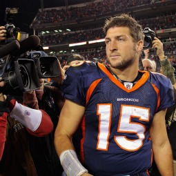 Quarterback Tim Tebow of the Denver Broncos is the focus of the cameras as he leaves the field after the game against the New England Patriots at Sports Authority Field at Mile High on Dec. 18 in Denver.