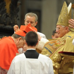 AUSPICIOUS DAY. Pope Benedict XVI bestows a red biretta, a four-cornered hat, on the head of new Cardinal Raymond Burke of the United States during a consistory ceremony in St. Peter's Basilica. Twenty-two men will receive the red hat Feb. 18.