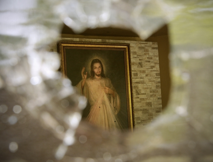 Above, A painting of Jesus Christ pierced with bullet holes is seen July 24 through an entrance point of a bullet hole in a window of the Jesus of Divine Mercy Church in Managua, Nicaragua. For nearly 15 hours overnight on July 13-14, heavily armed pro-government groups fired on the church while about 100 student protesters who had been forced out of the nearby university lay under pews in the main sanctuary.
