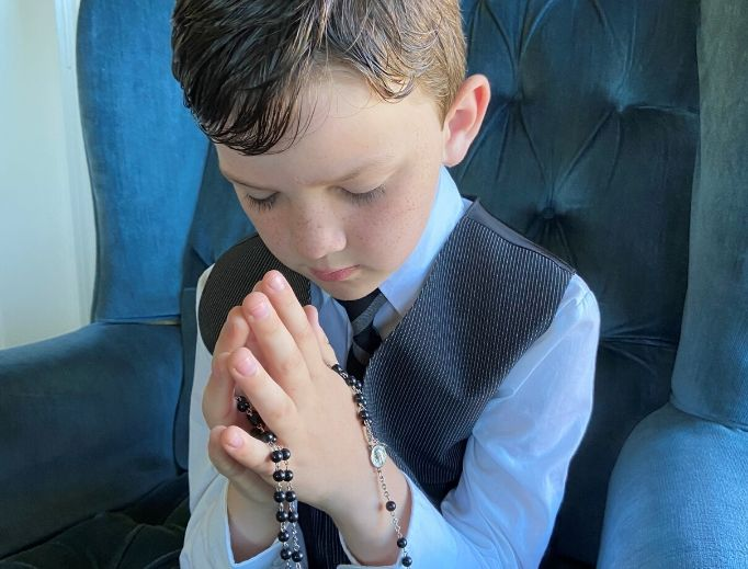 Fletcher Abner with his first Communion rosary. The rosary he is holding was made by his grandmother, Shirley Jones. She has made more than 20 for her grandchildren on their first Communion.