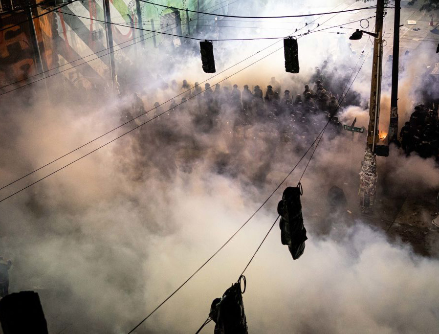 Tear gas fills the air as demonstrators clash with police near the Seattle Police Department's East Precinct on June 8.