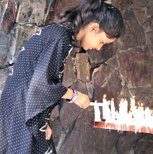 A young girl lights a candle at a Marian grotto in Pakistan.