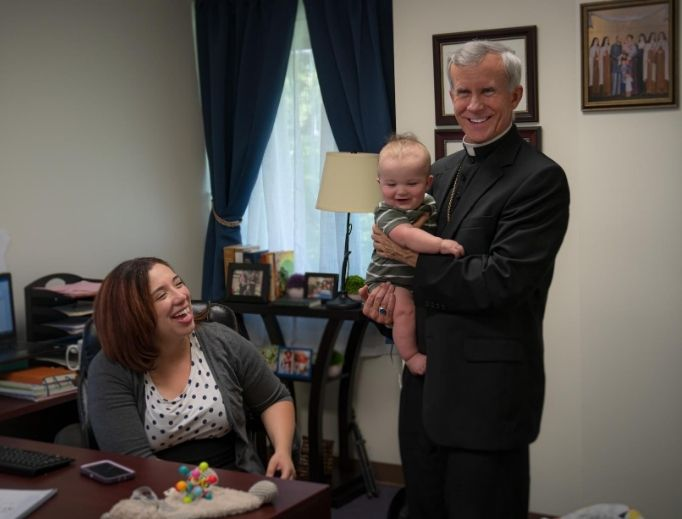 Deanna Johnston, director for family life, at the St. Philip Institute looks on as Bishop Joseph Strickland holds her baby.