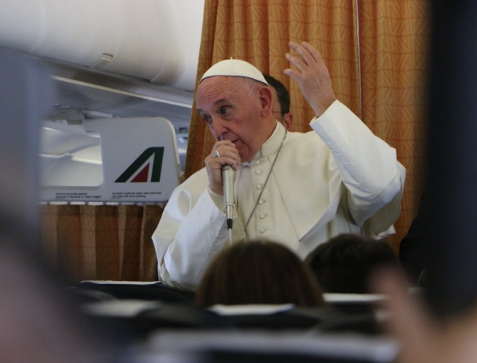 Pope Francis responds to journalists' questions aboard the papal plane returning to Rome Nov. 1.
