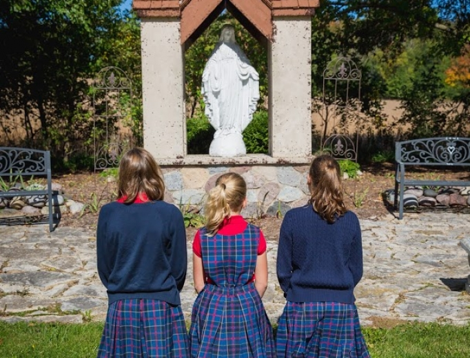 Above, students pray at the Trinity Academy outdoor Shrine to Our Lady of the Miraculous Medal, the site of the school Eucharistic procession. Below, Michael Moynihan instructs students in the classroom at The Heights.