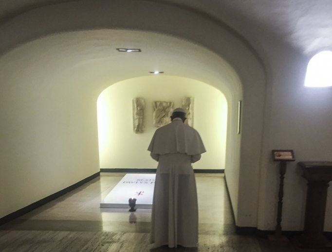 Pope Francis prays at the tomb of Blessed Paul VI beneath St. Peter's Basilica Aug. 6.