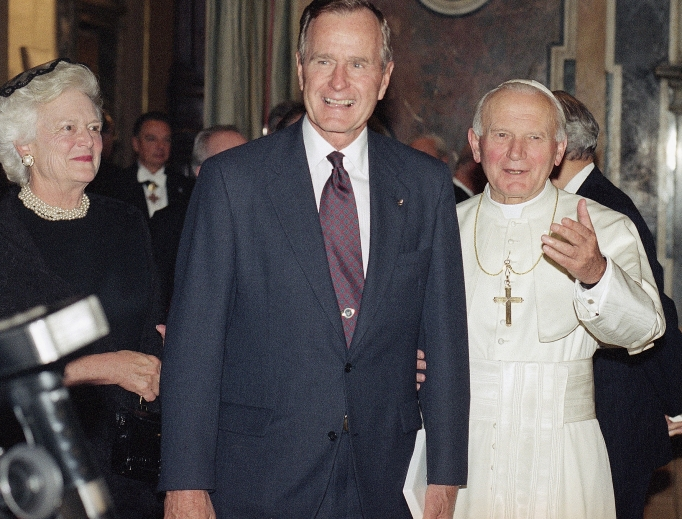 Pope John Paul II invites President George Bush, accompanied by his wife, Barbara, to meet members of the clergy gathered in the Vatican's Clementine Hall Nov. 8, 1991.