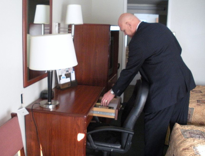 A member of The Gideons International leaves a Bible in a hotel room.