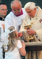 A girl kneels to receive Communion from the Pope.