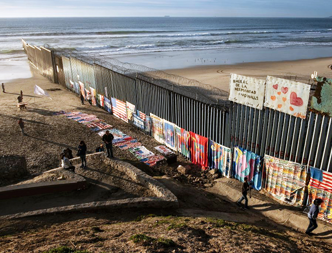 An exhibit by local artist Robenz and Central American migrants is on display on the beach next to a section of the US-Mexico border fence as seen from Tijuana, Mexico, on Jan. 8, 2019.