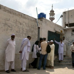 Members of the media and residents gather Aug. 23 outside a mosque near the locked family house of Rimsha Masih, a Pakistani Christian girl accused of blasphemy, on the outskirts of Islamabad.