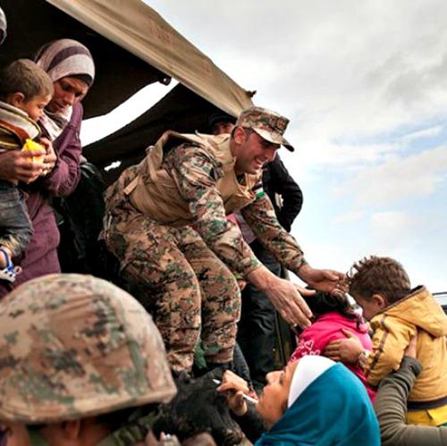 Jordanian troops and UNHCR officials help bring Syrian refugees to Jordan's Zaatari refugee camp.