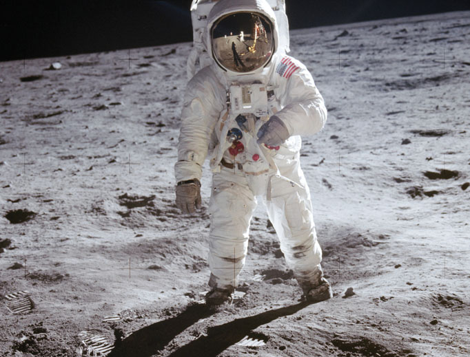 Above, Neil Armstrong (reflected in visor) and Edwin 'Buzz' Aldrin (in spacesuit) set foot on the moon on July 20, 1969. Also seen below, the astronauts captured a beautiful image of Earth rising above the moon's horizon from Apollo 11. Also below: the mission patch and other iconic moonshot photos, along with a solo photo of astronaut Armstrong. Bottom of page: All three Apollo 11 astronauts, Michael Collins (l) and Neil Armstrong (r) shown, and their wives attend an audience with Pope Paul VI in the Papal Library Oct. 16, 1969.