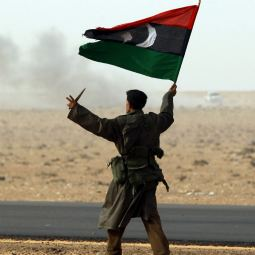A rebel fighter holds a Kingdom of Libya flag and a knife during battle with soldiers loyal to Libyan leader Col. Moammar Gadhafi near Ras Lanuf, a major oil port in Libya, March 4.