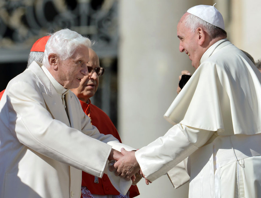 Pope Emeritus Benedict XVI speaks with Pope Francis during a Mass for elderly people in St. Peter's Square on Sept. 28, 2014.