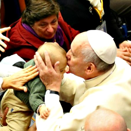Pope Francis kisses a baby at a Pontifical Council for Health Care conference on autism Nov. 22.