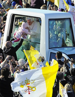 Pope Benedict XVI kisses infant Maria Tyszczak of Poland as he arrives to celebrate Mass at Bellahouston Park in Glasgow, Scotland, on the first day of his four-day visit to Great Britain.