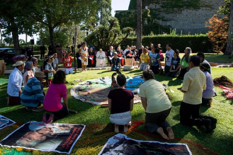 Participants kneel before bowing to a set of items during a tree-planting ceremony in the Vatican Gardens Oct. 3.