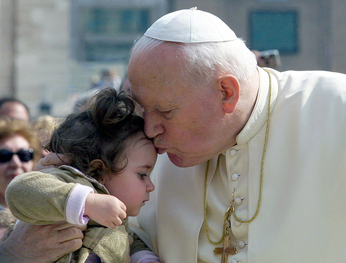 Pope John Paul II kisses a child as he arrives at St. Peter's Square at the Vatican, March 20, 2002, to preside his first open air weekly general audience of the year.