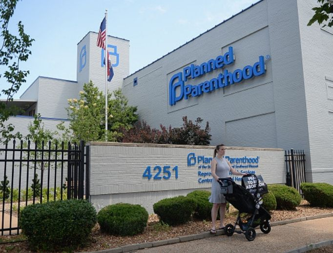 A woman stands with her child in a stroller during a pro-life rally outside the Planned Parenthood Reproductive Health Center on June 4 in St. Louis. The fate of Missouri's lone abortion facility will soon be decided.