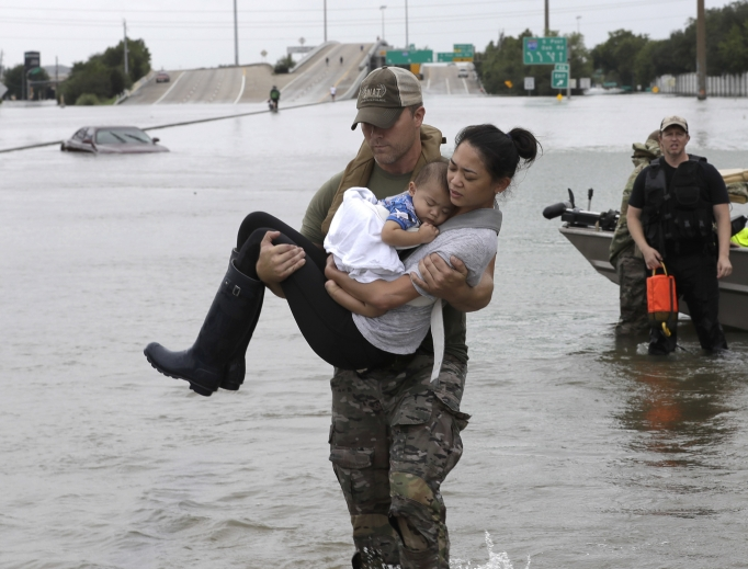 Houston Police SWAT officer Daryl Hudeck carries Catherine Pham and her 13-month-old son, Aiden, after rescuing them from their home surrounded by floodwaters from Tropical Storm Harvey Aug. 27 in Houston. The remnants of Hurricane Harvey sent devastating floods pouring into Houston Sunday as rising water chased thousands of people to rooftops or higher ground.