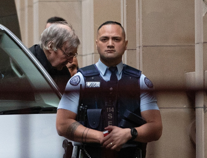 Australian Cardinal George Pell (c) is escorted into the Supreme Court of Victoria in Melbourne on Aug. 21, the day his appeal against sex-abuse charges was rejected.