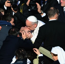 Pope Francis, greeting pilgrims gathered March 19 for his first Mass in St. Peter's Square, kisses a disabled man on the forehead.