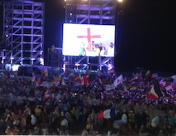 Pilgrims carry WYD cross to the altar during the opening Mass of World Youth Day July 23.