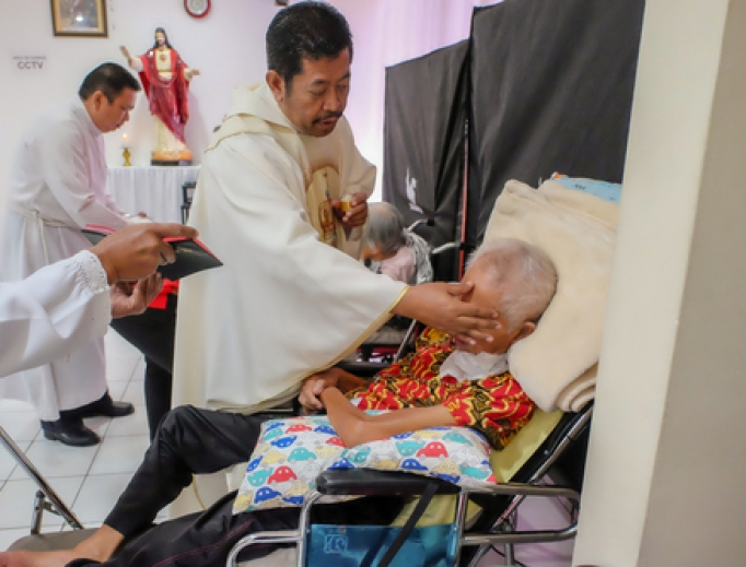 A priest anoints a very sick patient in a hospital.
