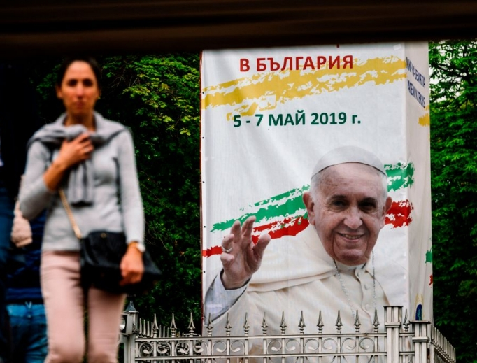 A woman walks past a billboard in downtown Sofia advertising Pope Francis' upcoming visit to Bulgaria, May 4. Pope Francis will arrive Sunday for a three-day visit to Bulgaria and North Macedonia.