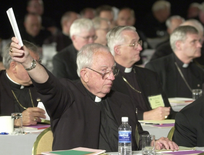 Bishop Walter Sullivan of Richmand, Virginia, holds up a ballot during the voting on the Charter for the Protection of Children and Young People at the U.S. Conference of Catholic Bishops' meeting in Dallas June 14. 2002. The charter celebrates its 15th anniversary this week and has made the U.S. Catholic Church one of the safest places for children anywhere in the world.