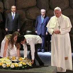 Two young students who live in Israel, Eva Kolodkina and Hoang Huy Nguyen, help Pope Francis lay a wreath May 26 at Israel's Yad Vashem Holocaust Memorial.