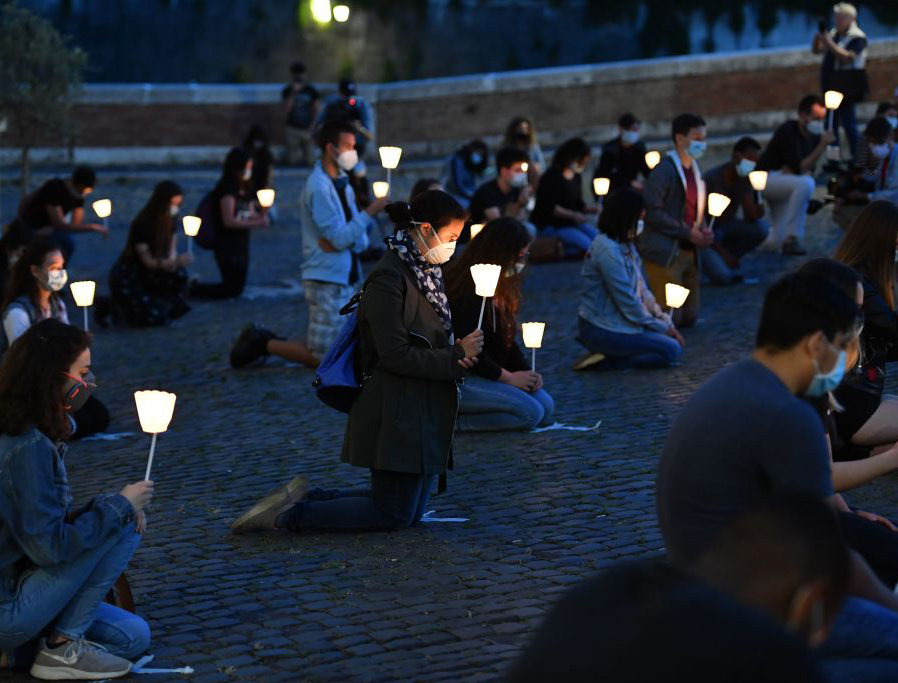 Young Catholics kneel Tuesday at a prayer vigil for George Floyd outside the San Bartolomeo church on Isola Tiberina island in Rome.