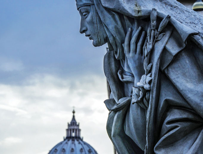 A statue of St. Catherine of Siena watches over St. Peter's Basilica in Rome, Italy.