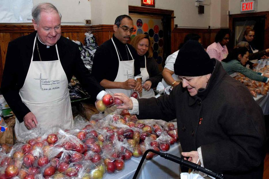Cardinal Edward Egan of New York helps out at a Catholic Charities Thanksgiving event in 2006.
