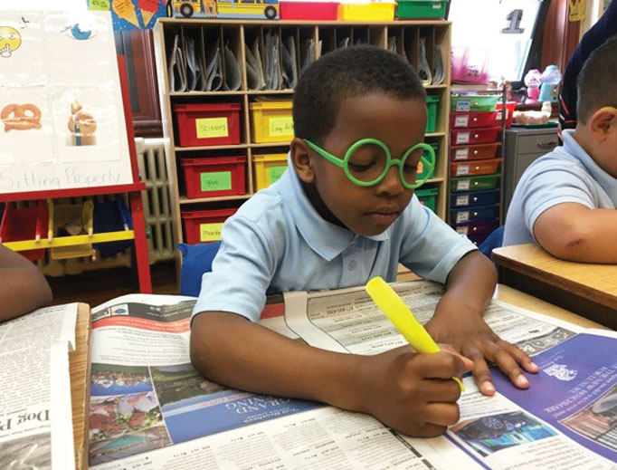 READING THE NEWS. Young readers wear their 'magic glasses' to look for words they recognize in the local paper.