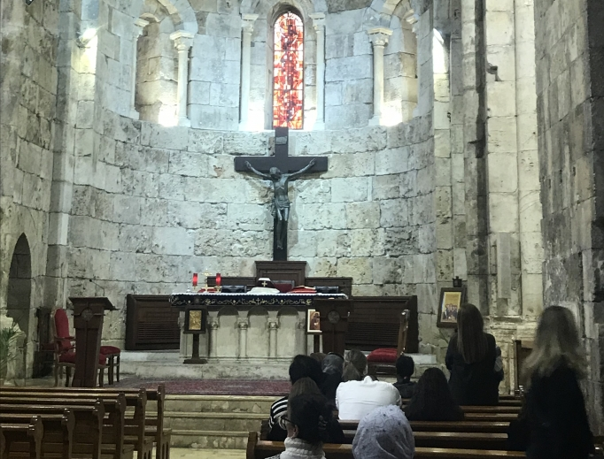 Above, worshippers pray in St. John-Marc Cathedral in Byblos; below, a portrait of St. Charbel graces the entrance of the Monastery of St. Maron.