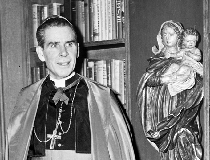 Bishop Fulton Sheen stands before a bookcase on the set of his Dumont television program.