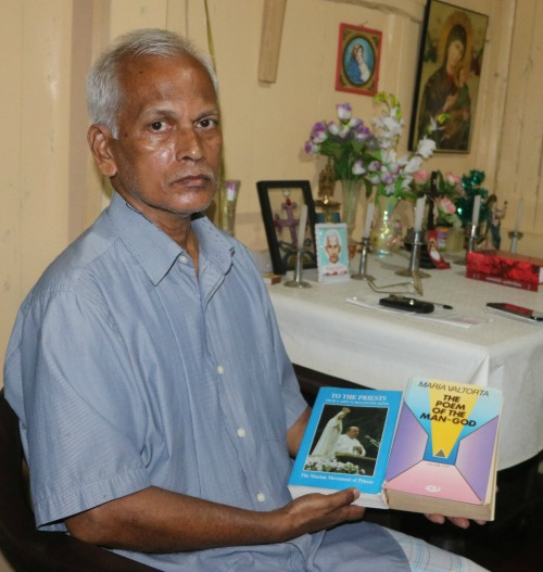 Mathew Uzhunnalil, the oldest brother of kidnapped Salesian Father Thomas Uzhunnalil, sits with a prayer book on March 28 in the family's ancestral home in Ramapuram, India.