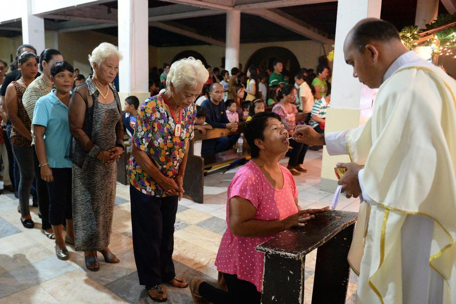 Survivors of Super Typhoon Haiyan receive Holy Communion in the Philippine village of San Joaquin in Palo on Dec. 24, 2013.