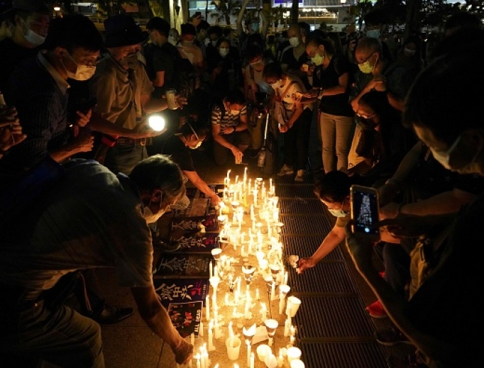 People light candles as they attend a vigil in Victoria Park in Hong Kong on June 4, 2020, after the annual remembrance that traditionally takes place in the park to mark the 1989 Tiananmen Square crackdown was banned on public health grounds because of the coronavirus pandemic.