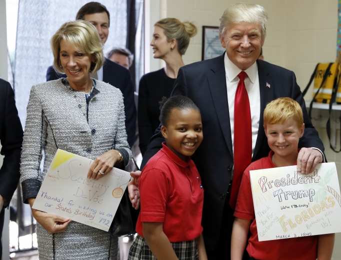 President Donald Trump and Education Secretary Betsy DeVos pose with fourth graders Janayah Chatelier, 10, left, Landon Fritz, 10, after they received cards from the children, during a tour of St. Andrew Catholic School March 3 in Orlando, Florida.