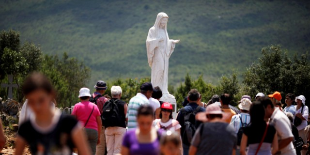 Pilgrims flock around a statue of Mary at Medjugorje.