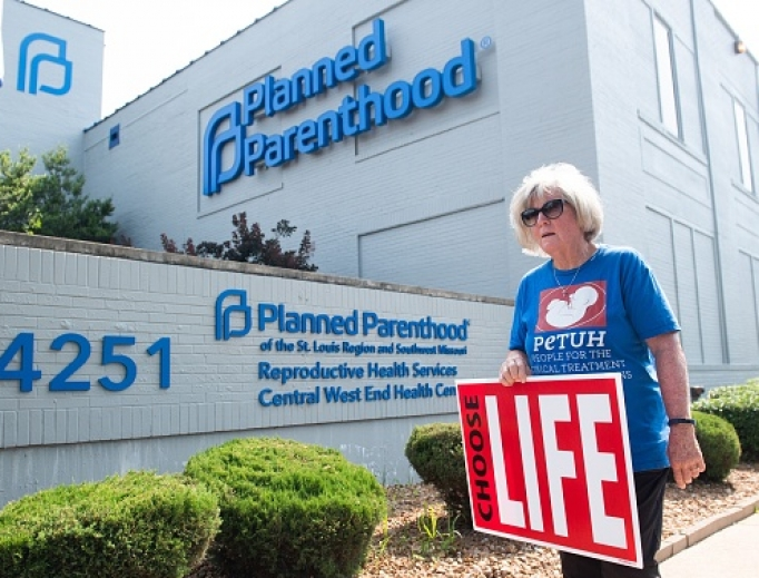 Above, a pro-life demonstrator walks outside the Planned Parenthood Reproductive Health Services Center in St. Louis May 31.  A coalition of pro-abortion groups has released a document outlining vision of abortion with no restrictions, no religious exemptions, and funded by the government.
