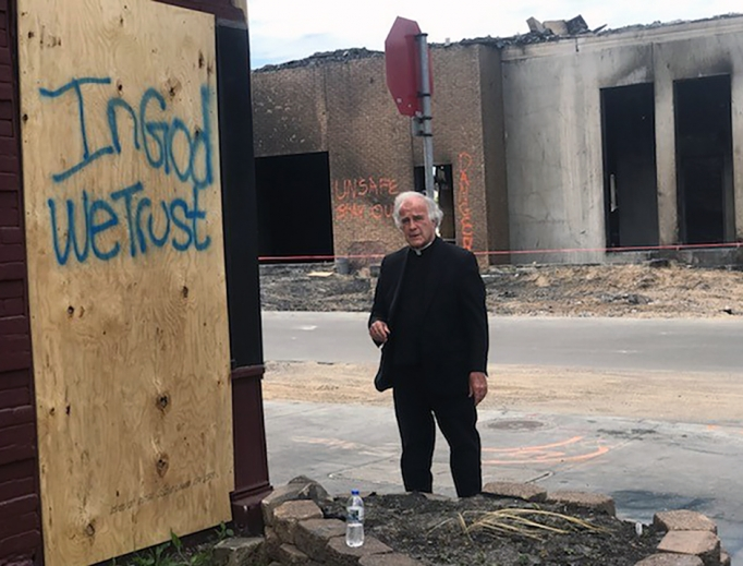 Above, Dominican Father Joseph Gillespie, the pastor of St. Albert the Great in south Minneapolis, stands by a hopeful message amid destruction in his parish neighborhood. The area was looted during violent protests following the death of George Floyd at the end of May.
